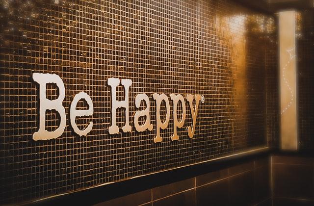 """značka, nápis """"be happy"""" na stěně"""