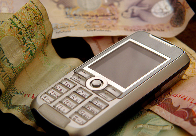 starý telefon položený uprostřed bankovek